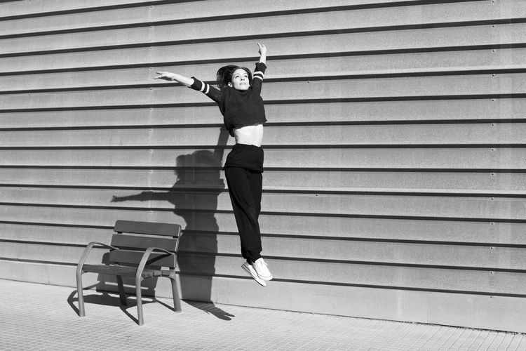 Woman Jumping From Chair By Wall