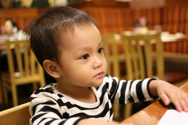 Close-up of cute boy sitting at restaurant