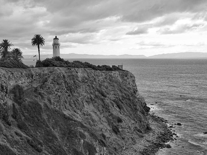 Point vicente lighthouse on cliff by sea against cloudy sky