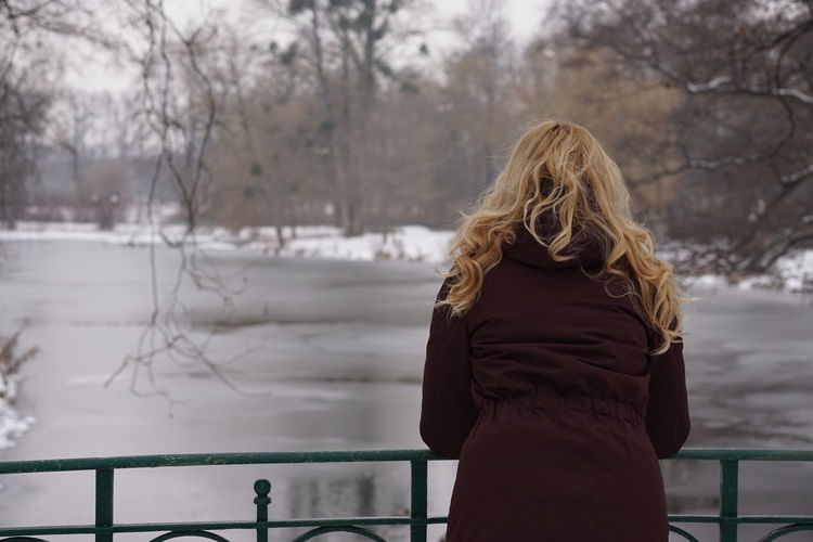 Rear View Of Woman Leaning On Railing At Footbridge Over Frozen Lake During Winter