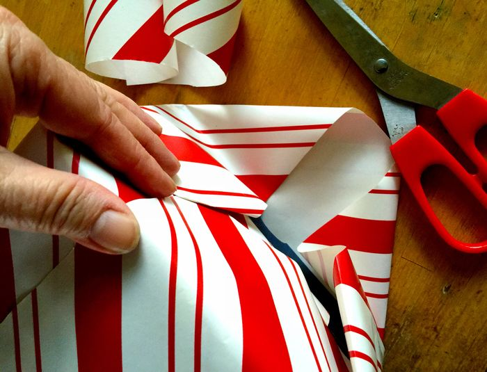 Wrapping a package with red and white peppermint-striped paper using red-handled scissors Christmas Close-up Closeup Colorful Fingers Hand Holding Peppermint-striped Phone Camera POV Red Scissors Seasonal White Wrapping Presents