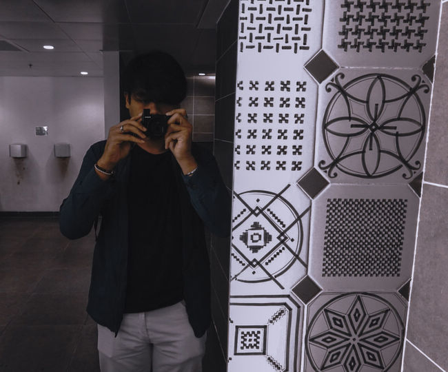 Man photographing while standing against wall