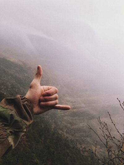 Close-up of person doing shaka sign on mountain during foggy weather