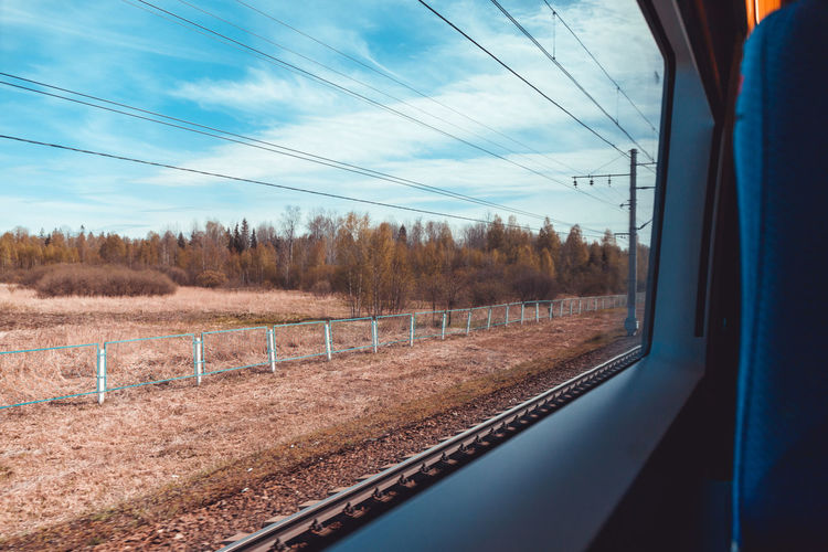 Train Sky Rail Transportation Tree Transportation Train - Vehicle Mode Of Transportation Vehicle Interior No People Cloud - Sky Nature Public Transportation Plant Window Electricity  Cable Transparent Travel Landscape Passenger Train Track Outdoors Power Supply