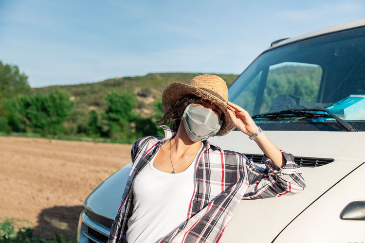 Portrait of woman wearing mask while standing by vehicle