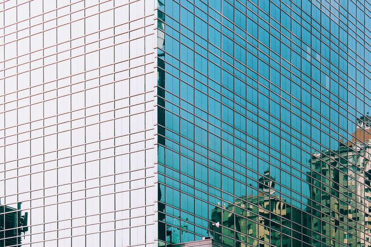 Low angle view of reflection in modern glass building in the city
