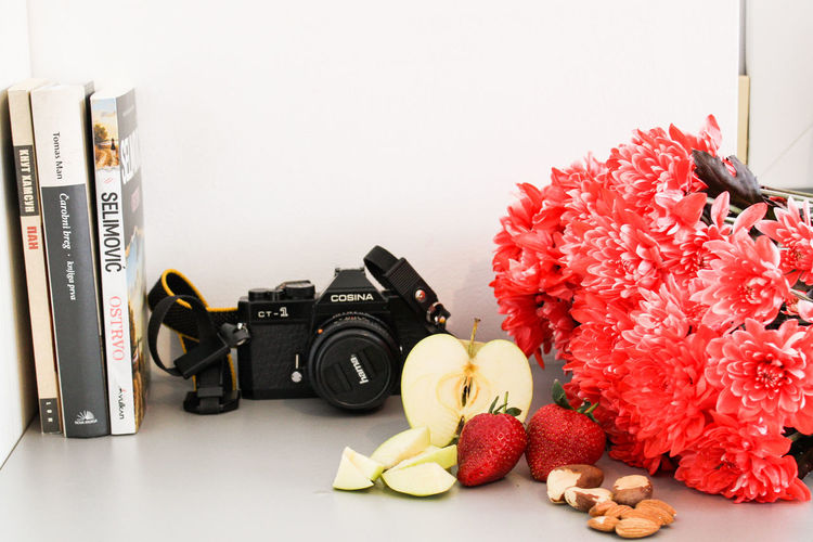 Close-up of red and wine on table against white background