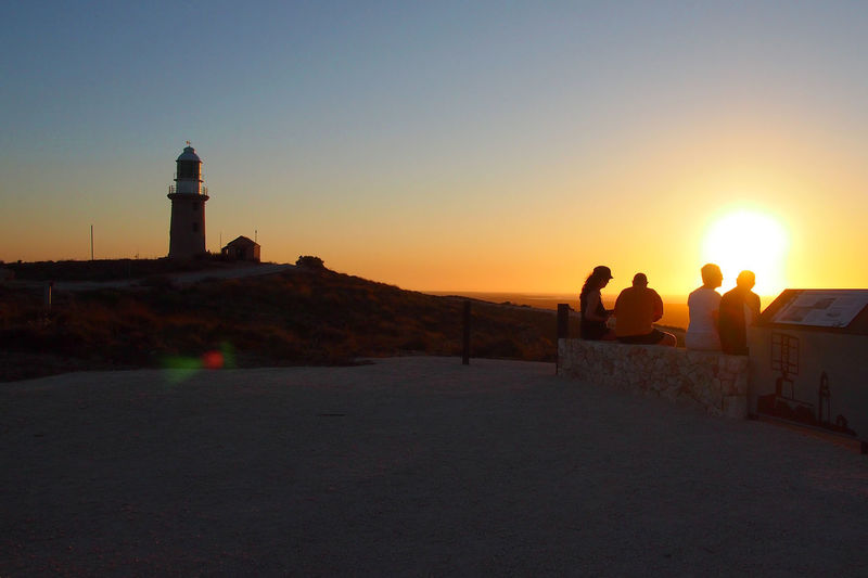 People on lighthouse at sunset