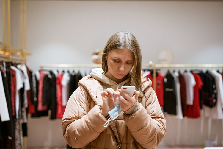 Woman using phone while standing at store