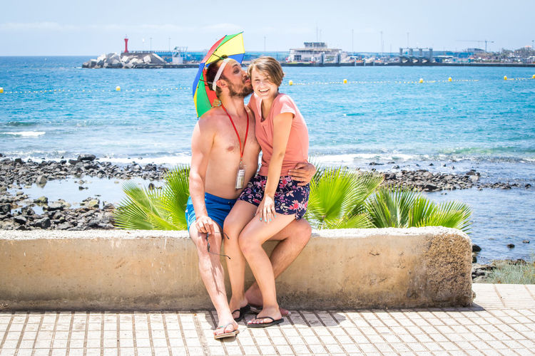 Cheerful couple sitting on retaining wall against sea