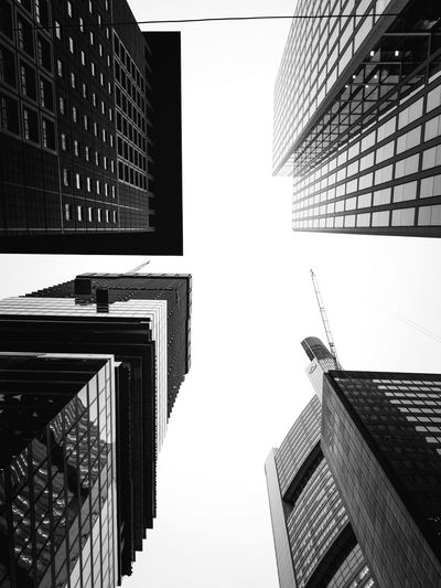 Directly below shot of buildings in city against sky