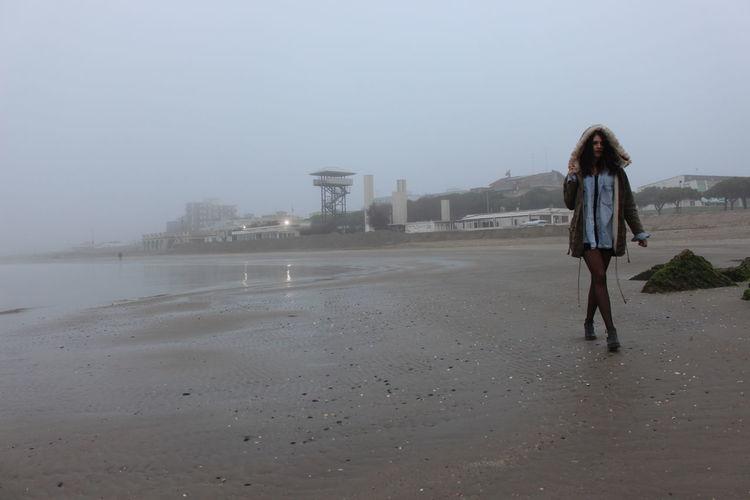 Woman Walking On Beach Against Sky In Foggy Weather