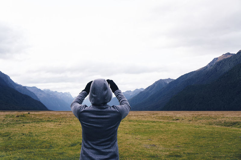 Rear View Of Person In Hooded Jacket Photographing Mountains Against Sky