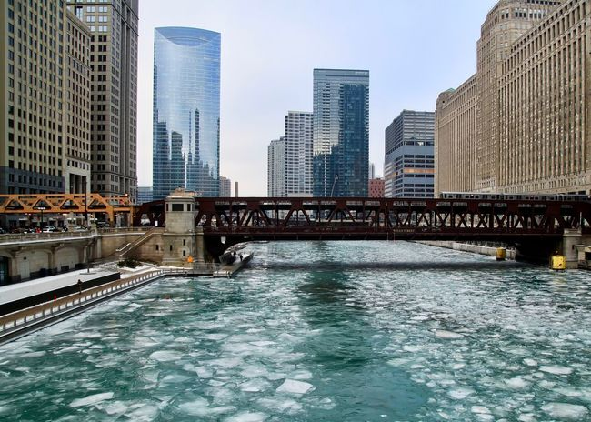 Chicago el train passes over a frozen river with ice chunks bobbing after boat drove through it. Chicago River Chicago El Chicago Loop Downtown Chicago Elevated Track Architecture Bridge - Man Made Structure Building Exterior Built Structure City Cityscape Day Downtown District Elevated Train Frozen River Ice Chunk Modern No People Outdoors River Sky Skyscraper Urban Skyline Water Waterfront
