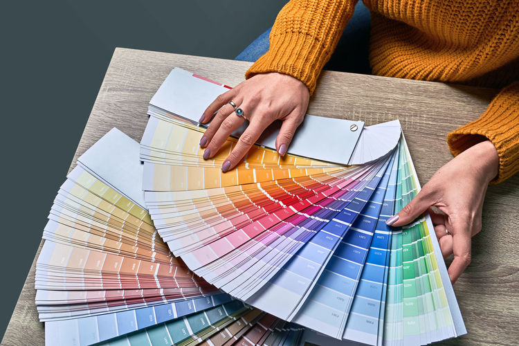 Midsection of woman holding color swatch at home