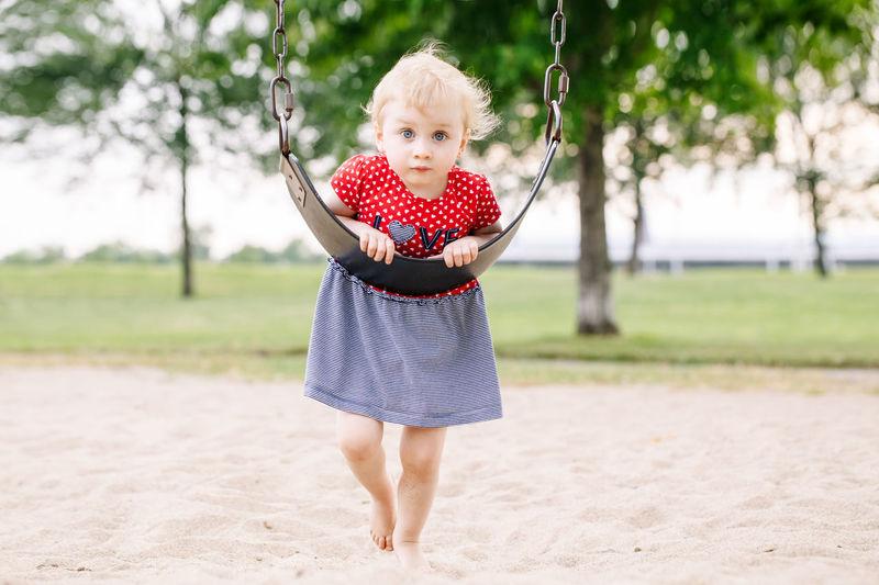 Full length portrait of cute girl leaning on swing over sand
