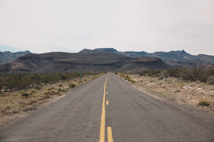 Empty Country Road Passing Through Arid Landscape Against Sky
