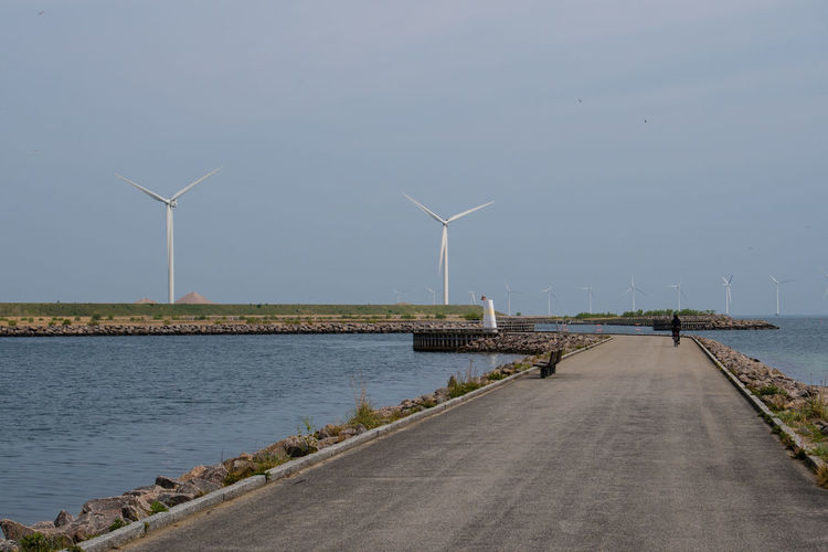 Windmills by sea against sky