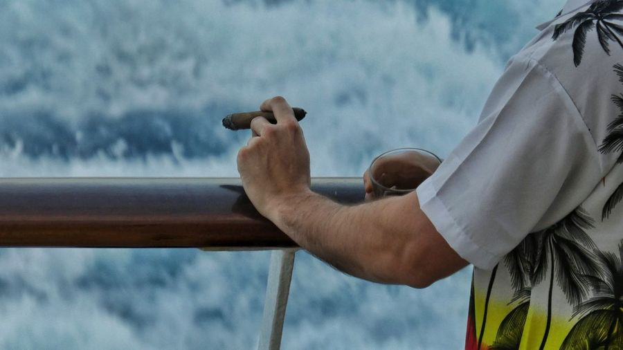Midsection Of Man Holding Drink While Smoking Cigar By Railing In Boat Against Sea