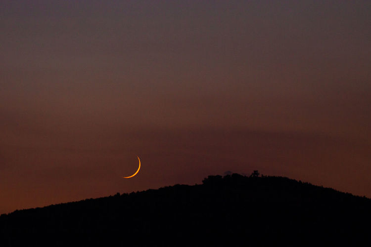 Moon crescent over hill. Astronomy Beauty In Nature Cloud - Sky Copy Space Crescent Dark Idyllic Moon Nature Night No People Non-urban Scene Orange Color Outdoors Scenics - Nature Silhouette Sky Space Sunset Tranquil Scene Tranquility