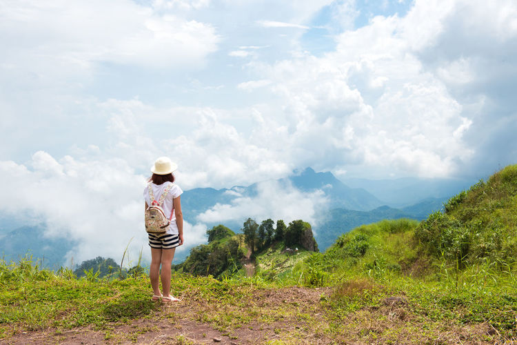 Woman Enjoying Nature on grass meadow on top of mountain in Thailand Cloud - Sky Sky One Person Beauty In Nature Leisure Activity Scenics - Nature Real People Plant Rear View Mountain Nature Lifestyles Standing Casual Clothing Tranquility Tranquil Scene Land Green Color Day Tree Outdoors Looking At View