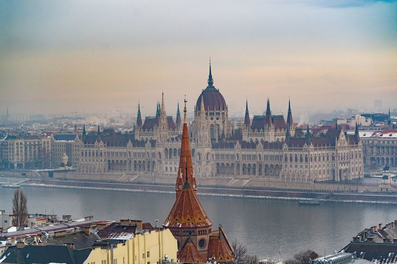High angle view of hungarian parliament building by danube river against sky during sunset