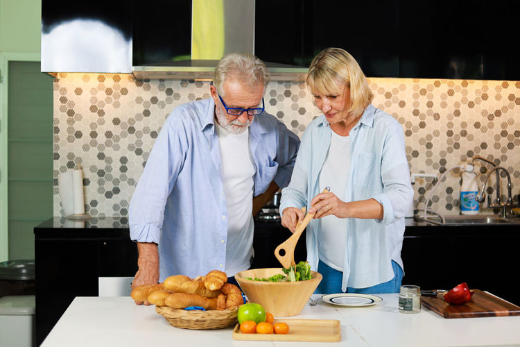 Adult Beard Colorful Cooking Couple Dinner Food Fruit Gray Groceries Grocery Hair Happy Healthy Herbs Home Hood House Husband Indoors  Ingredients Inside Kitchen Lifestyle Man Mature Meal Old Older  People Preparing Red Senior Seniors Shopping Sweater Together Vegetables Wife Woman Yellow