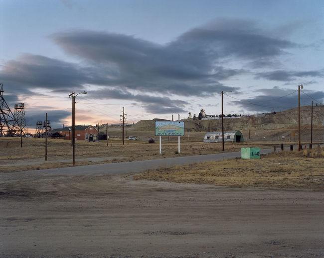 Road by buildings on field against sky