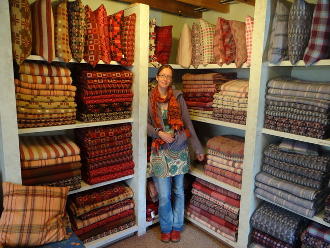 Melin Tregwynt Abundance Casual Clothing Choice Wool Material Wool For Sale Freshness Front View Full Length Indoors  Large Group Of Objects Leisure Activity Lifestyles Mid Adult Women One Person Real People Retail  Shelf Small Business Stack Standing Store Variation Welsh Wool Blanket
