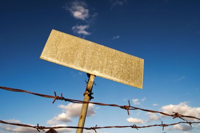Sky Low Angle View Rusty No People Blue Nature Clear Sky Road Sign Outdoors Day Fences & Beyond Fence Wire Fencing Thorn