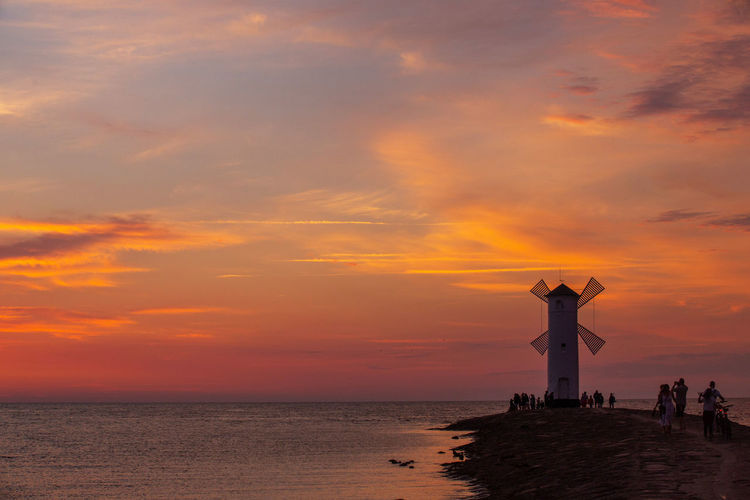 Baltic Sea Stawa Mlyny Architecture Building Exterior Built Structure Cloud - Sky Guidance Holiday Horizon Horizon Over Water Human Arm Lighthouse Nature Orange Color Outdoors Scenics - Nature Sea Silhouette Sky Sunset Tower Travel Destinations Trip Vacations Water