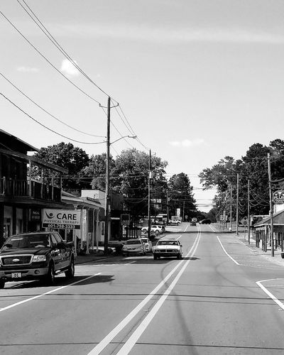 small town life Tree City Road Telephone Line Car Street Sky Building Exterior Architecture Built Structure Stop Sign Parking Sign Road Sign Road Signal Traffic Arrow Sign Speed Limit Sign Green Light Warning Sign Road Marking Parking Red Light Street Light Road Warning Sign One Way Stoplight