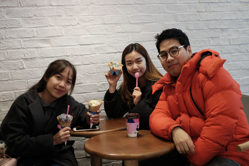 Brick Wall Cafe Day Drink Eating Eyeglasses  Food Food And Drink Friendship Front View Holding Indoors  Leisure Activity Lifestyles Looking At Camera Portrait Real People Sitting Smiling Sweet Food Table Togetherness Young Adult Young Men Young Women