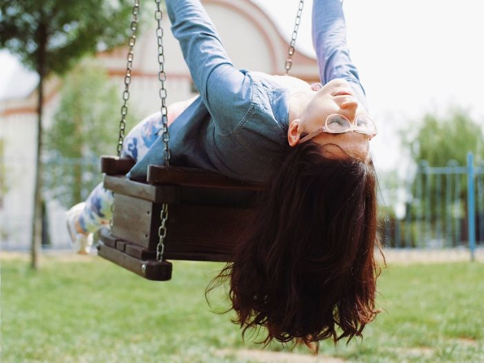 Carefree woman lying on swing outdoors