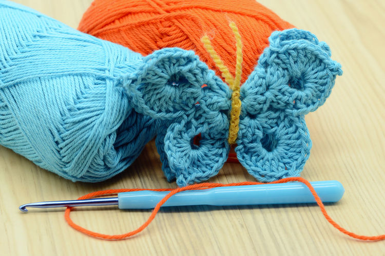 Close-Up Of Crochet With Wool On Table