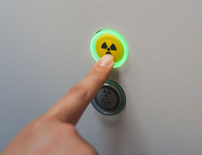 Close-up of hand pressing radioactive warning symbol button