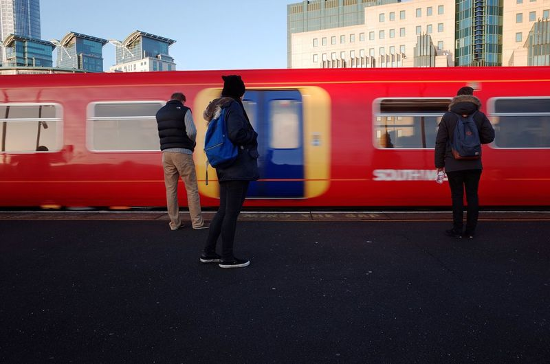 Full length of red train in city