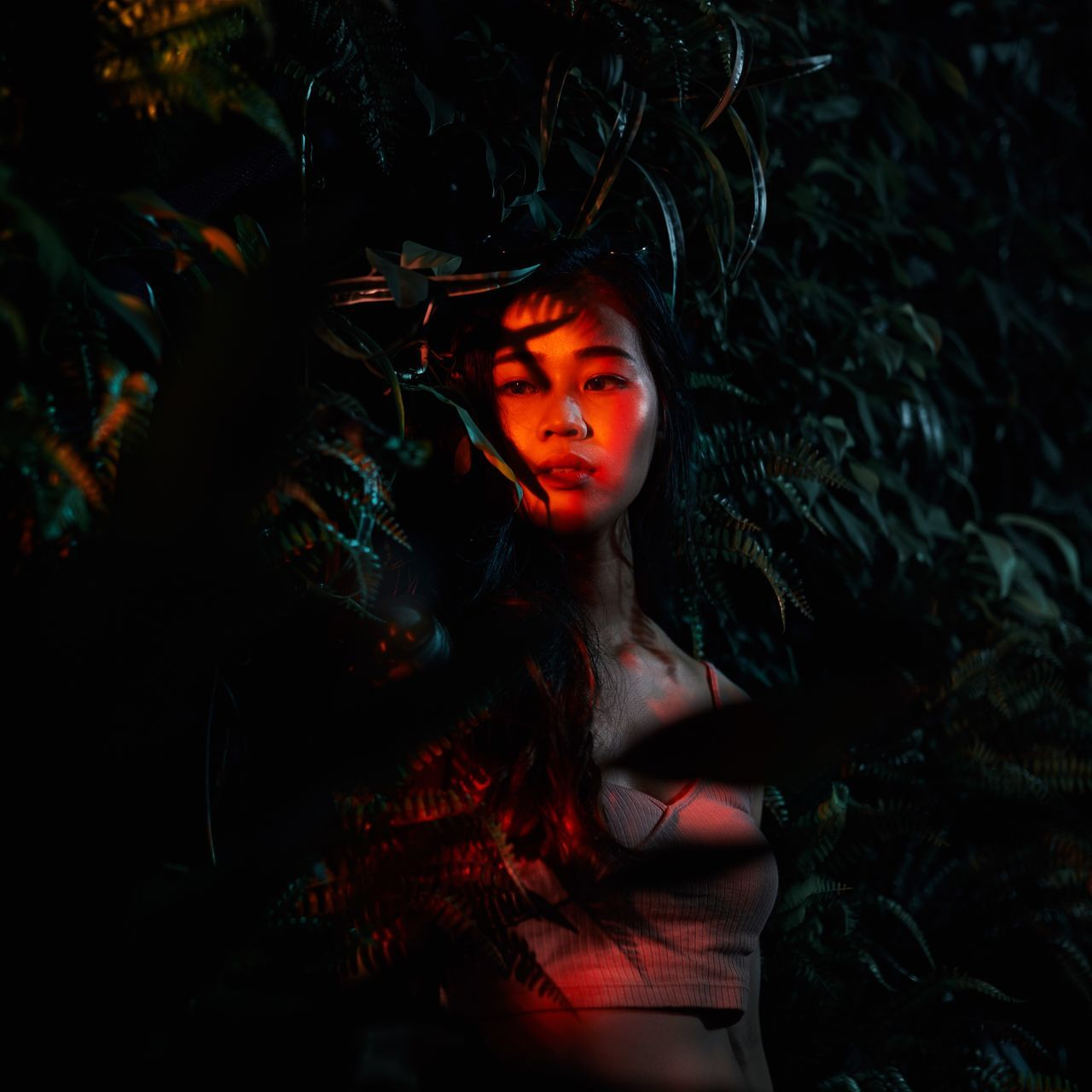 Thoughtful young woman standing by plants at night