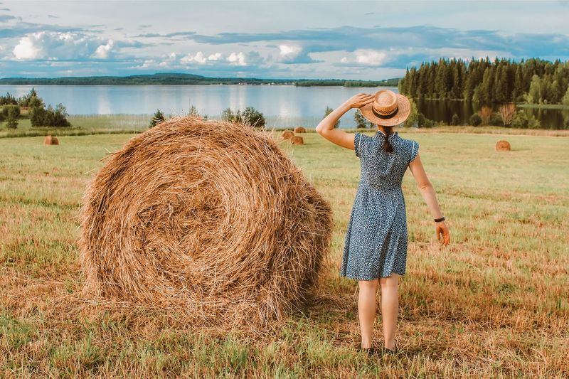 A girl in a dress and a straw hat stands with her back to the hay field. summer landscape