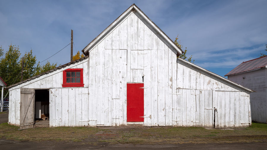 Exterior of barn outside house against sky