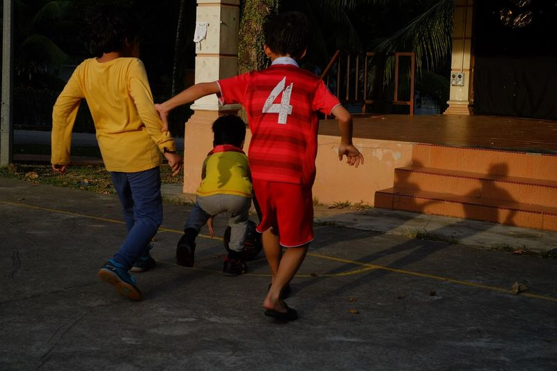 Street Football Streetphotography Full Length Rear View Child Street Childhood Red Men Architecture Togetherness Walking Real People People City Casual Clothing Built Structure Family The Art Of Street Photography