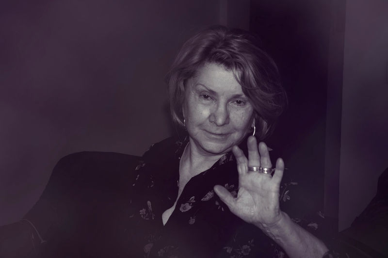 Portrait of woman gesturing while sitting at home