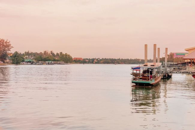 A Thai boat is floating on the river in Bangkok Thailand. Thailand Thai Boat Raft River Transportation People Asian  Evening Tidal Water Water Wave Stream Current Pier Old Boat Ship Bangkok City Village Flood Sky Sunset Sunlight Waterfront