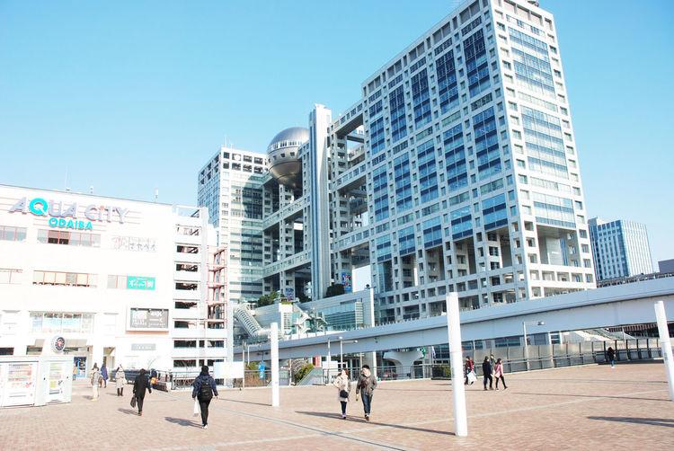 People walking on modern building against clear sky