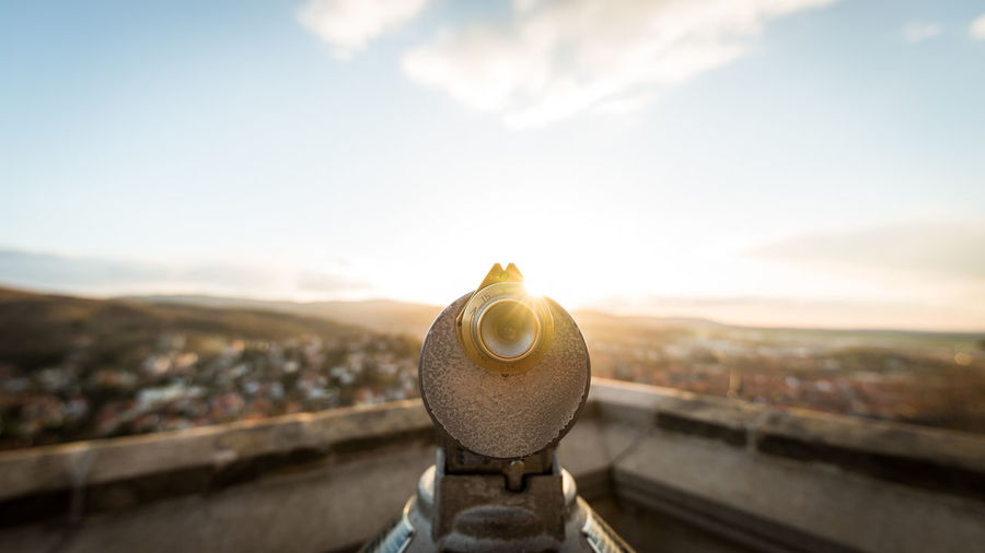 Close-Up Of Coin-Operated Binoculars Against Cityscape During Sunset