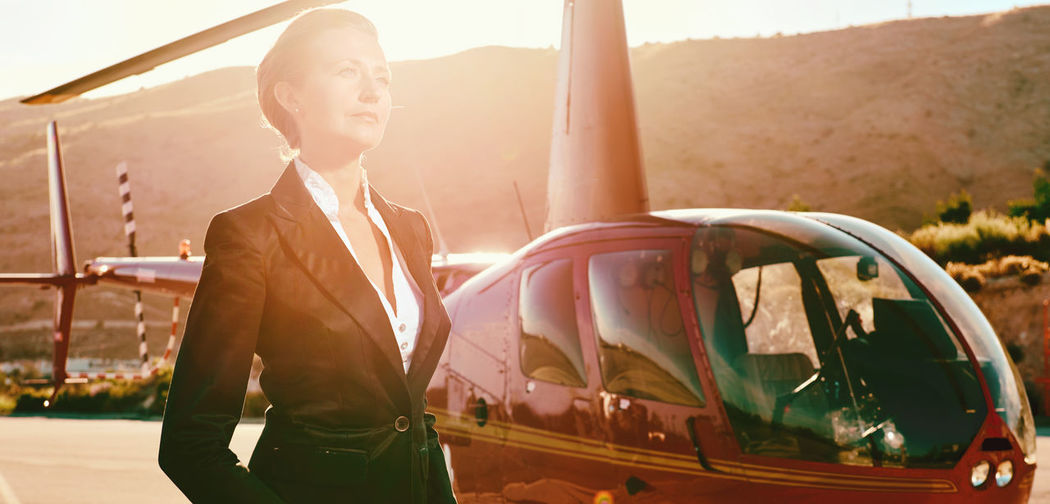 Businesswoman looking away while standing by helicopter during sunny day