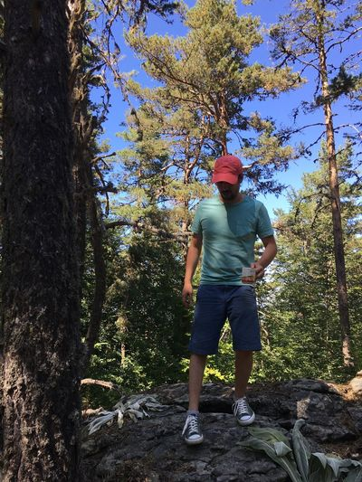 Full length of man standing on rock in forest