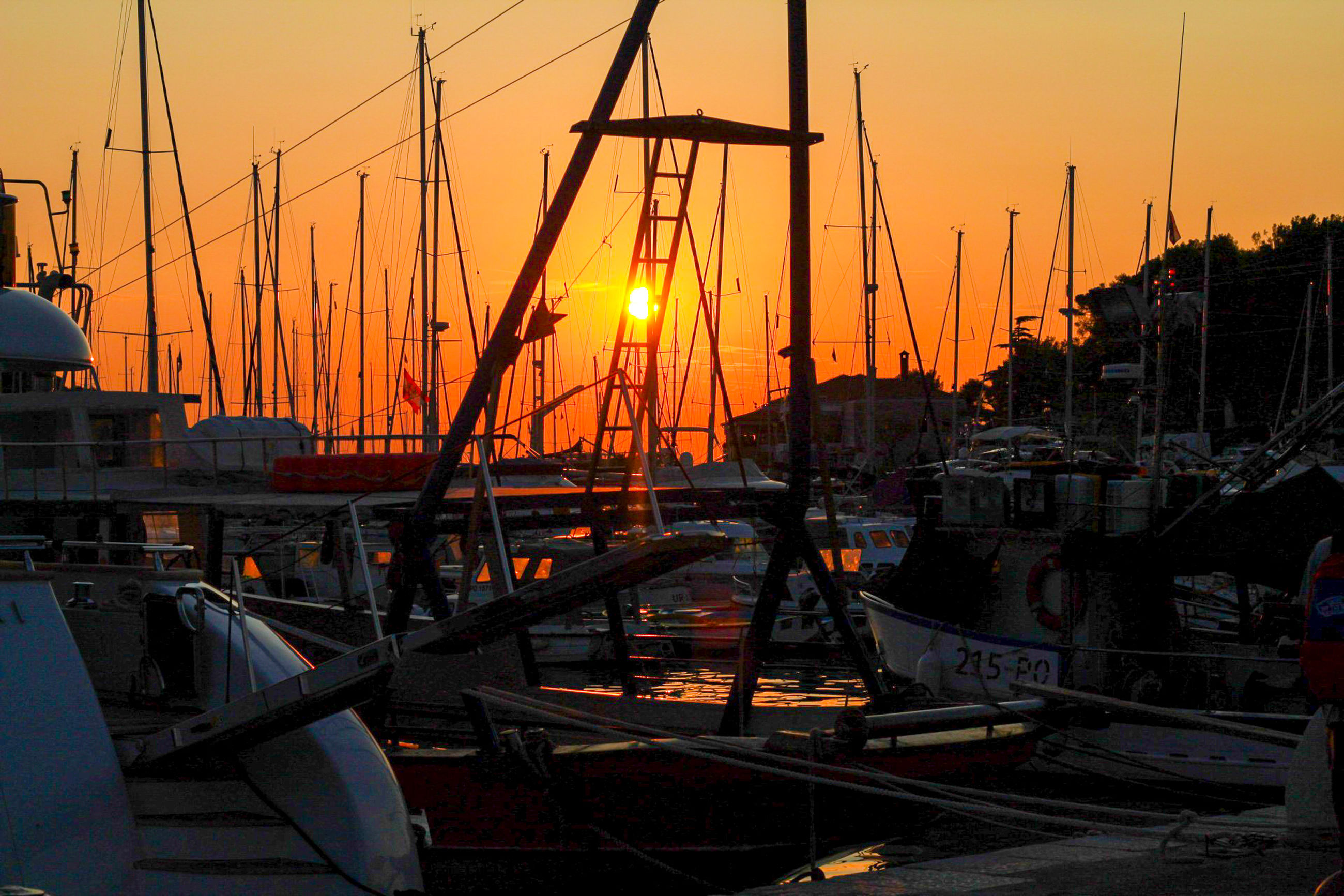 sunset, sky, nautical vessel, mode of transportation, transportation, water, orange color, pole, harbor, sailboat, nature, no people, mast, moored, architecture, sea, outdoors, sun, beauty in nature, bright, marina, yacht, rigging, port