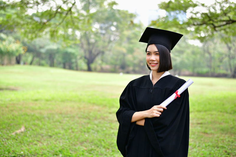 Graduation Concept. Graduated students on graduation day. Asian students are smiling happily on the graduation day. Students wear graduation gowns in the garden Get A Degree Academic Achievement Adult Asian  Bachelor Background Beautiful Beauty Cap Ceremony Certificate Cheerful Chinese College Degree Diploma Education Educational Educational Attainment Educational Institution Female Girl Gown Grad Graduate Graduated Graduating Graduation Happiness Happy Hat Japanese  Knowledge Learning Lifestyle Outdoors People person Portrait Progress School Smile Smiling Student Study Success Successful University Woman
