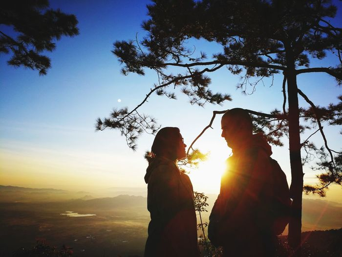 Couple Standing On Mountain Against Sky During Sunset